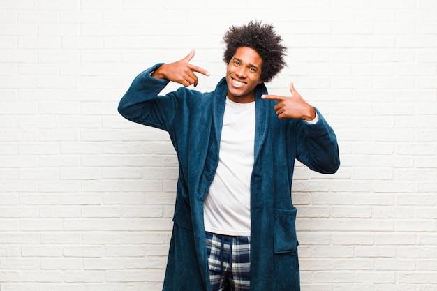 Jonge zwarte mens die pyjama's met toga dragen die vol vertrouwen glimlachen die op eigen brede glimlach, positieve, ontspannen, tevreden houding tegen bakstenen muur wijzen