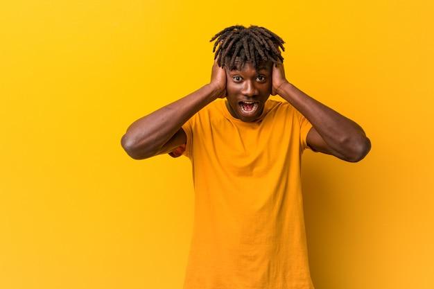 Jonge zwarte mens die rastas over gele achtergrond draagt die oren behandelt met handen die niet te hard geluid proberen te horen.