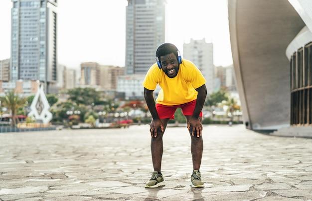 Jonge zwarte mens die rust na snel lopende training nemen terwijl het luisteren van muziek met hoofdtelefoons