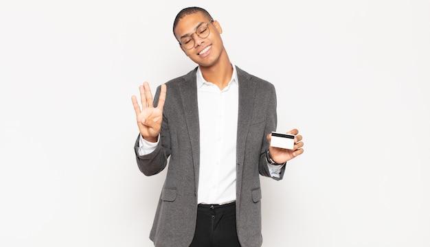 Jonge zwarte mens die vriendelijk glimlacht en kijkt, nummer vier of vierde met vooruit hand toont, aftellend