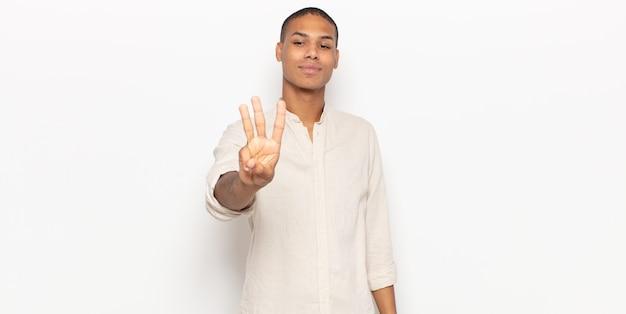 Jonge zwarte mens die vriendelijk glimlacht kijkt, nummer drie of derde met vooruit hand toont, aftellend