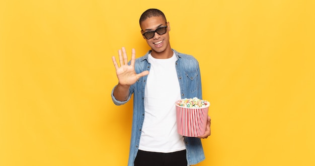 Jonge zwarte mens die vriendelijk glimlacht kijkt, nummer vijf of vijfde met vooruit hand toont, aftellend
