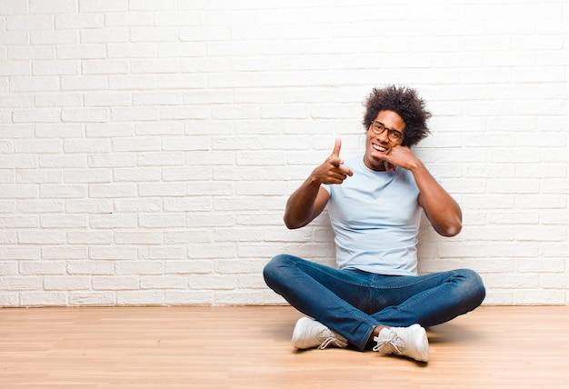 Jonge zwarte mens die vrolijk glimlachen en aan camera richten terwijl het telefoneren van u later gebaar, thuis sprekend op telefoonzitting op de vloer