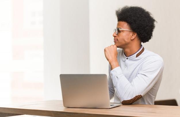 Jonge zwarte mens die zijn laptop aan de kant gebruiken die aan voorzijde kijken