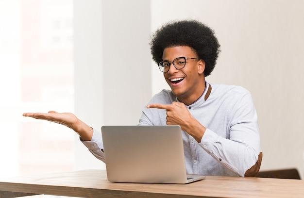 Jonge zwarte mens die zijn laptop met behulp van iets met de hand houdt