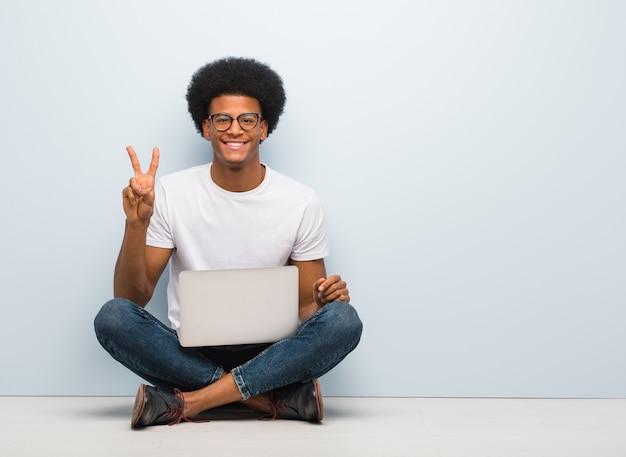 Jonge zwarte mensenzitting op de vloer met laptop die nummer twee toont