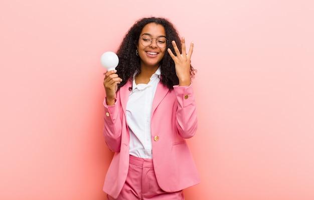 Jonge zwarte met een gloeilamp die een idee op roze muur heeft