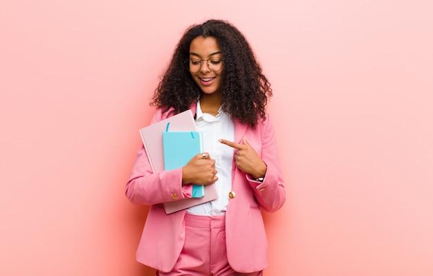 Jonge zwarte mooie bedrijfsvrouw met boeken tegen roze muur