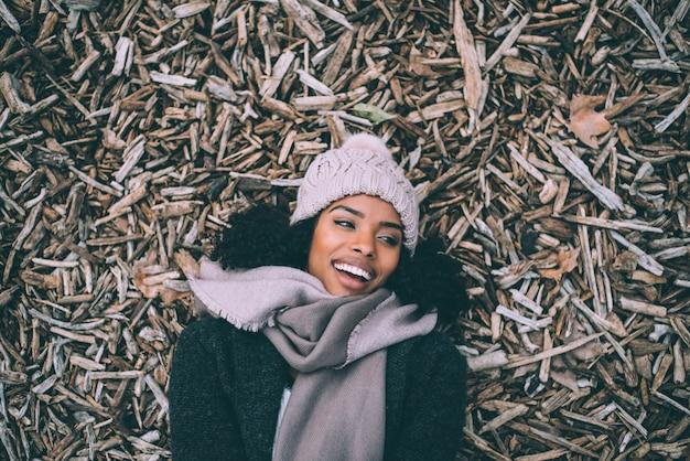 Jonge zwarte mooie vrouw die op stukken van hout ligt