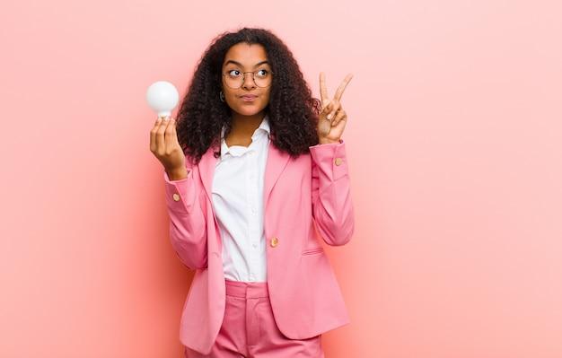 Jonge zwarte mooie vrouw met een gloeilamp die een idee heeft tegen roze muur