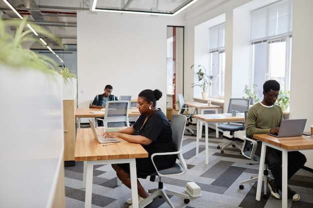 Jonge zwarte ondernemers die op laptops werken aan bureaus in een coworkingcentrum in de open ruimte
