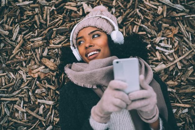 Jonge zwarte op de mobiele telefoon die op stukken van hout ligt