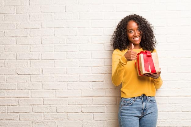 Jonge zwarte opgewekt en opgewekt, glimlachend en haar duim opheffend, concept succes en goedkeuring, ok gebaar