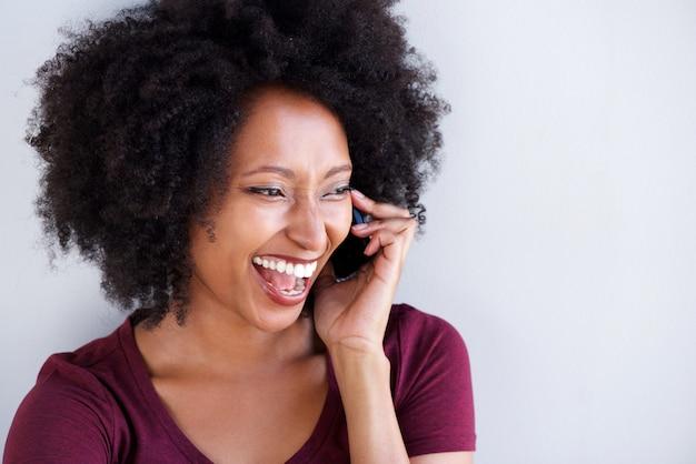 Jonge zwarte praten op telefoon en lachen