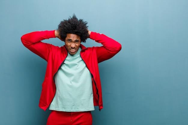Jonge zwarte sport man gevoel gestrest, bezorgd, angstig of bang, met handen op het hoofd, in paniek bij vergissing