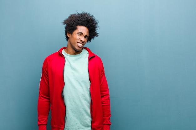 Jonge zwarte sport man gevoel verbaasd en verward, met een domme, verbijsterde uitdrukking op zoek naar iets onverwachts tegen grunge muur