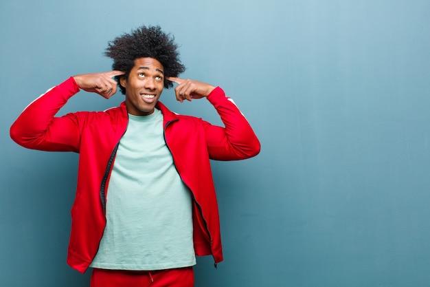Jonge zwarte sport man gevoel verward of twijfelen, zich te concentreren op een idee, hard denken, op zoek om ruimte te kopiëren aan de zijkant tegen grunge muur
