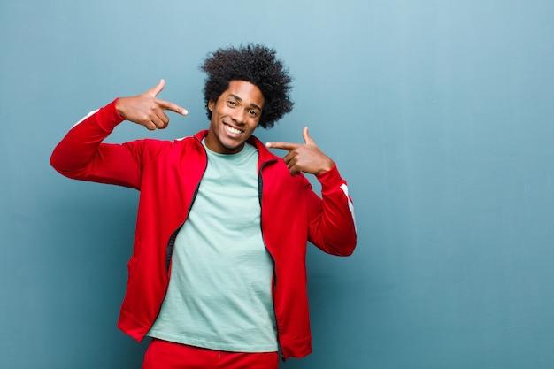 Jonge zwarte sport man glimlachend vol vertrouwen wijzend op eigen brede glimlach, positieve, ontspannen, tevreden houding tegen grunge muur