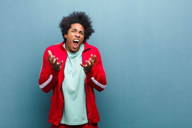 Jonge zwarte sport man op zoek wanhopig en gefrustreerd, gestresst, ongelukkig en geïrriteerd, schreeuwen en schreeuwen tegen grunge muur