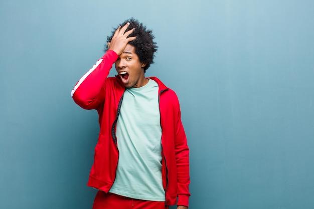 Jonge zwarte sport man palm naar voorhoofd te verhogen denken oeps, na het maken van een domme fout of herinneren, dom voelen tegen grunge muur