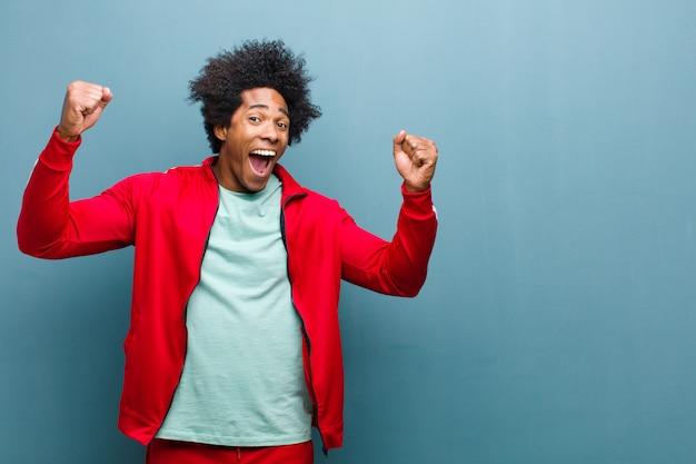 Jonge zwarte sport man triomfantelijk schreeuwen, ziet eruit als opgewonden, blij en verrast winnaar, vieren tegen grunge muur