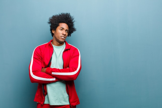 Jonge zwarte sport man twijfelen of denken, lip bijten en zich onzeker en nerveus voelen, op zoek naar ruimte aan de zijkant