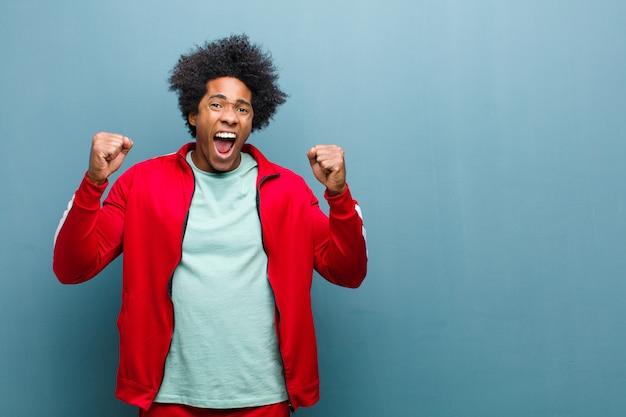 Jonge zwarte sport man voelt zich blij, verrast en trots, schreeuwt en viert succes met een grote glimlach