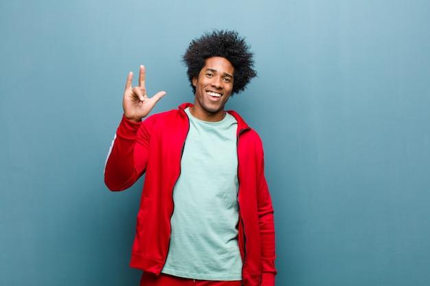Jonge zwarte sport man voelt zich gelukkig, leuk, zelfverzekerd, positief en opstandig, waardoor rock of heavy metal bord met hand tegen grunge muur