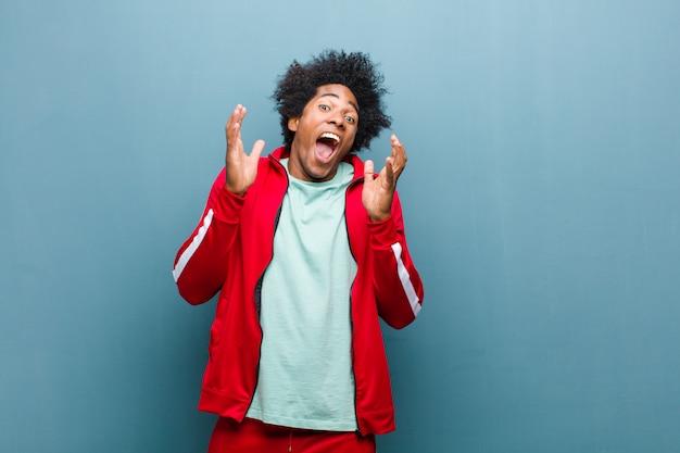 Jonge zwarte sport man voelt zich geschokt en opgewonden, lachen, verbaasd en gelukkig vanwege een onverwachte verrassing tegen grunge muur