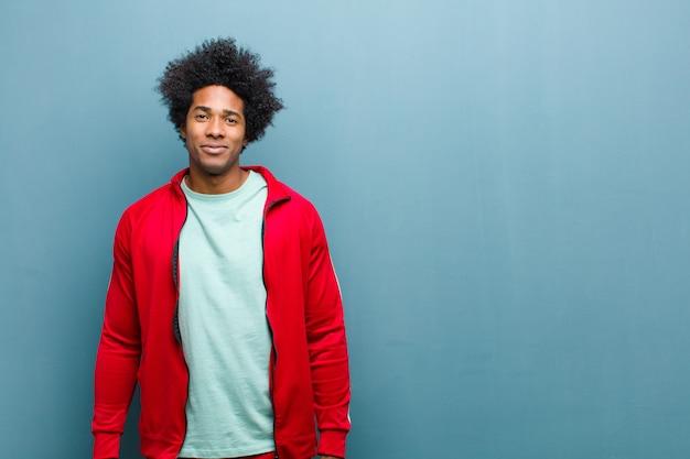 Jonge zwarte sportenmens die positief en vol vertrouwen glimlachen, kijkend tevreden, vriendschappelijk en gelukkig op grungemuur