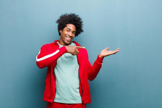 Jonge zwarte sportenmens die vrolijk glimlachen en aan exemplaarruimte op palm aan de kant richten, een voorwerp tonen of adverteren tegen grungemuur
