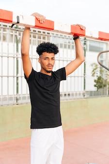 Jonge zwarte sportman die op voetbaldoel houden bij stadion