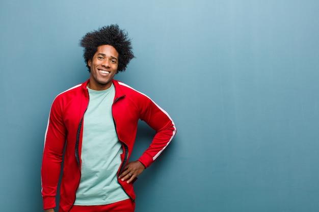 Jonge zwarte sportmens die gelukkig met een hand op heup en zekere, positieve, trotse en vriendschappelijke houding tegen grungemuur glimlacht