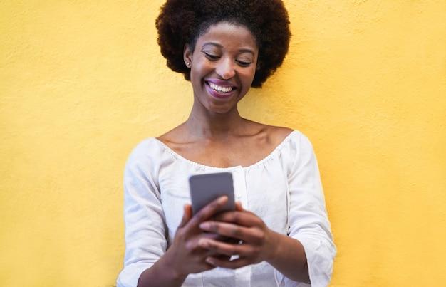 Jonge zwarte status geïsoleerd over geel gebruikend slimme mobiele telefoon
