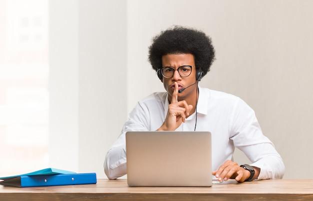 Jonge zwarte telemarketer die een geheim bewaart of om stilte vraagt