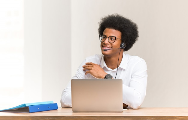 Jonge zwarte telemarketer glimlachende zeker en kruisend wapens, omhoog kijkend
