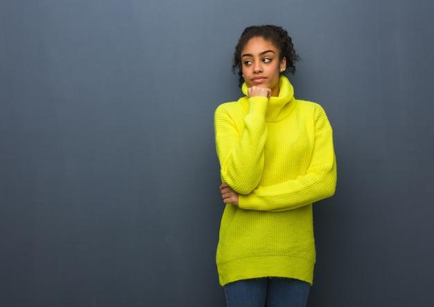 Jonge zwarte twijfelende en verwarde vrouw