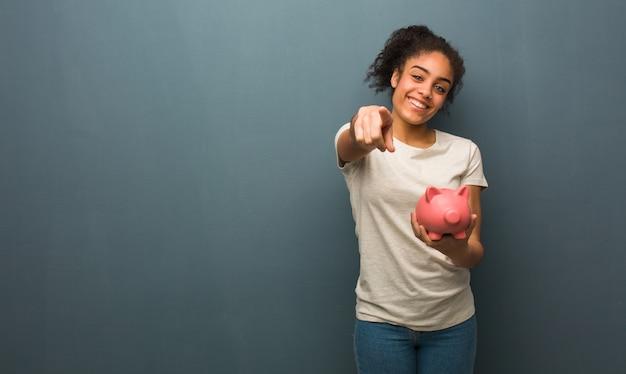 Jonge zwarte vrolijk en glimlachend. ze houdt een spaarvarken vast.