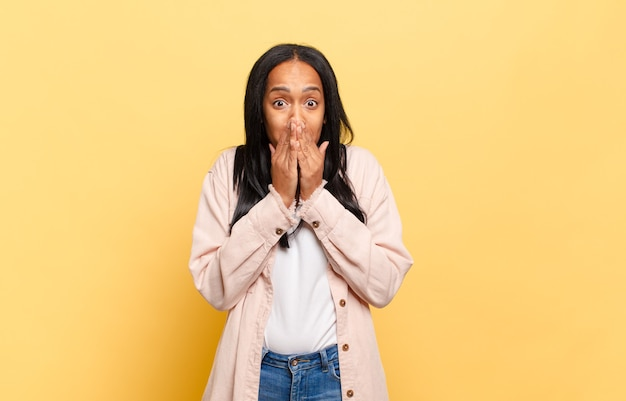 Jonge zwarte vrouw blij en opgewonden, verrast en verbaasd over de mond met handen, giechelend met een schattige uitdrukking