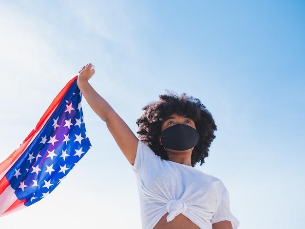 Jonge zwarte vrouw buitenshuis, met een beschermend masker tegen coronavirus en met een amerikaanse vlag