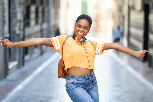 Jonge zwarte vrouw danst op straat in de zomer. meisje dat alleen reist.