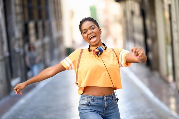 Jonge zwarte vrouw danst op straat in de zomer.