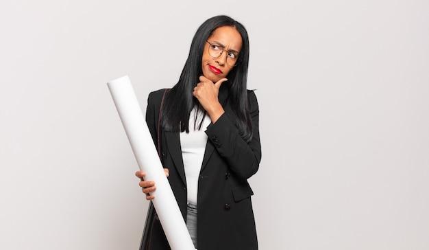 Jonge zwarte vrouw denkt, voelt zich twijfelachtig en verward, met verschillende opties, zich afvragend welke beslissing ze moet nemen. architect concept