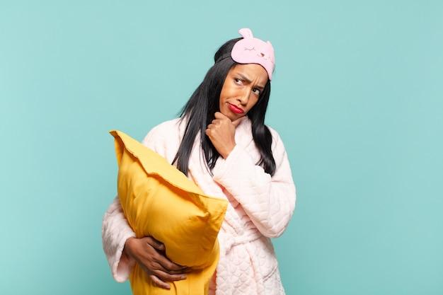 Jonge zwarte vrouw denkt, voelt zich twijfelachtig en verward, met verschillende opties, zich afvragend welke beslissing ze moet nemen. pyjama concept