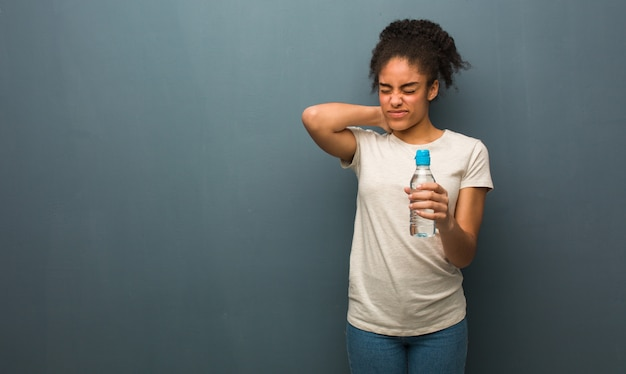 Jonge zwarte vrouw die aan nekpijn lijdt. ze houdt een fles water vast.