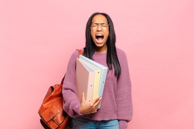 Jonge zwarte vrouw die agressief schreeuwt, erg boos, gefrustreerd kijkt