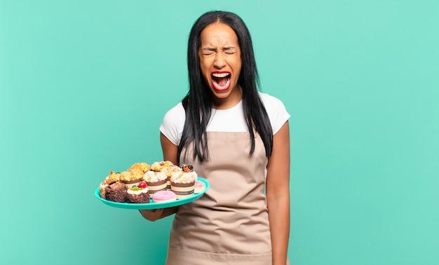 Jonge zwarte vrouw die agressief schreeuwt, erg boos, gefrustreerd, verontwaardigd of geïrriteerd kijkt en nee schreeuwt. bakkerij chef-kok concept