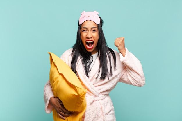 Jonge zwarte vrouw die agressief schreeuwt met een boze uitdrukking of met gebalde vuisten om succes te vieren. pyjama concept