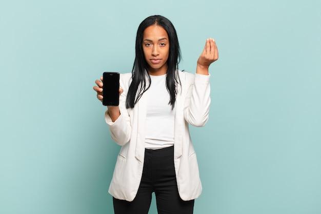 Jonge zwarte vrouw die capice of geldgebaar maakt en u vertelt uw schulden te betalen!. slimme telefoon concept