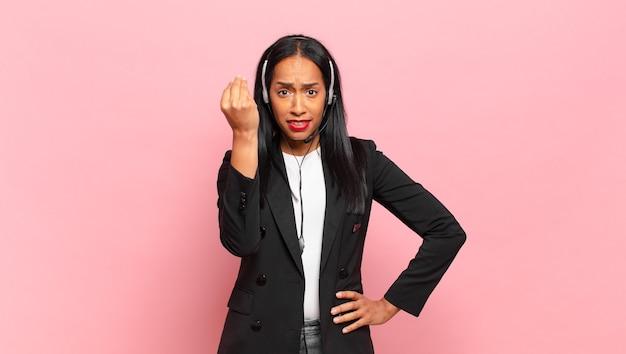 Jonge zwarte vrouw die capice of geldgebaar maakt en u vertelt uw schulden te betalen!. telemarketing concept